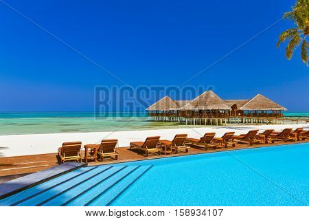 Pool and cafe on Maldives beach - nature vacation background