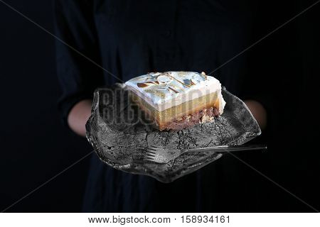 Woman holding tray with slice of delicious cake on dark background