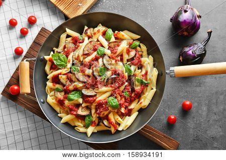 Pan with tasty macaroni, kitchen board and products on grey table, top view