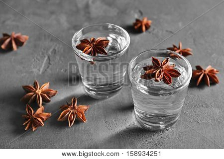 Vodka with anise on grey textured background