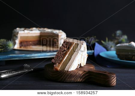 Slice of delicious cake with chocolate, nuts and pear topping on wooden board