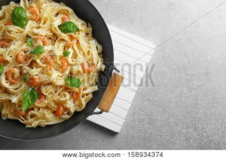 Pan with tasty alfredo pasta and kitchen board on grey table, top view