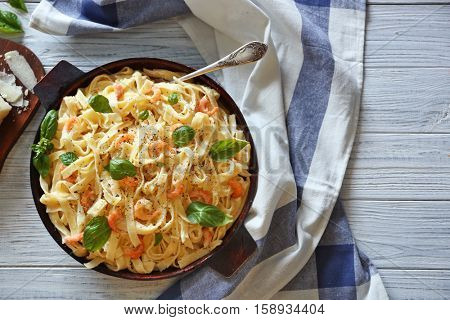 Pan with tasty alfredo pasta, napkin and fork on wooden table, top view