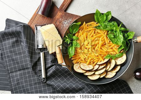 Pan with ingredients for tasty pasta, napkin, kitchen board and grater on grey table, top view