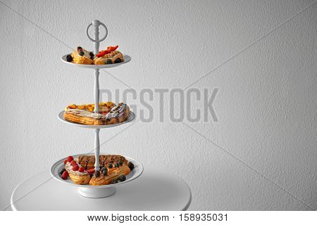 Delicious colourful eclairs with berries on dessert stand