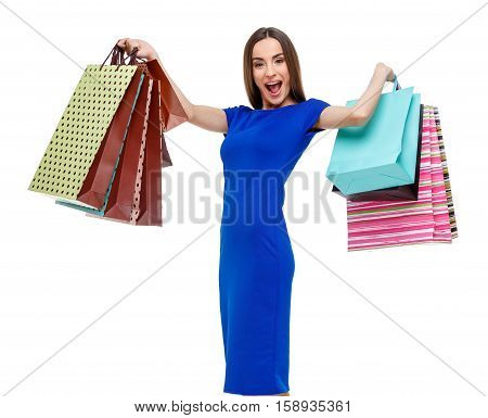 Portrait of young happy smiling woman with shopping bags, isolated over grey background