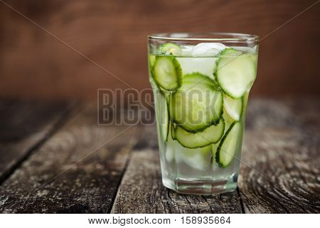 Detox water with cucumber and lemon on wooden background.