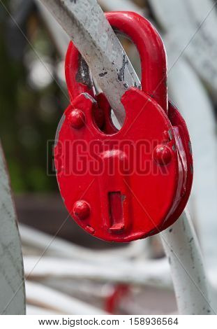 Red iron lock on a white fence close-up