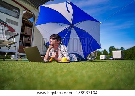 Woman on the grass, looking at the laptop under umbrella near the campe. Caravan car Vacation. Family vacation travel, holiday trip in motorhome
