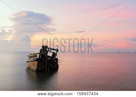 Abandoned shipwreck at morning in the sea