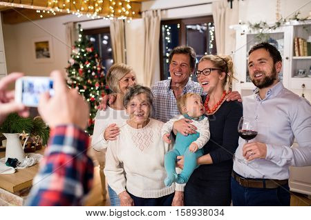 Beautiful big family celebrating Christmat together at home being photohrphed by unrecognizable man with smart phone. Illuminated Christmas tree behind them.