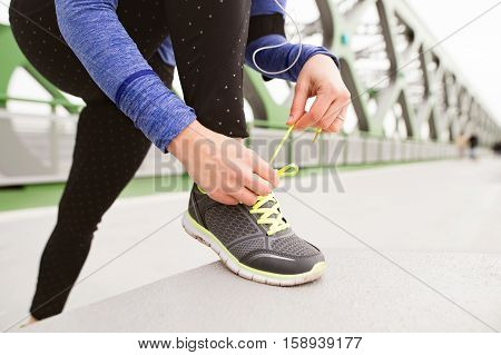 Unrecognizable runner in the city tying shoelaces on green steel bridge. Close up.
