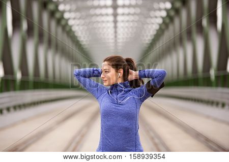 Beautiful young runner with armband and earphones, listening music, in the city warming up and stretching on green steel bridge.