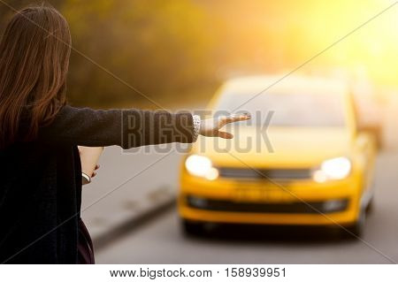 Brunette woman hand gesture catches taxi on the road. Image with lens flare effect