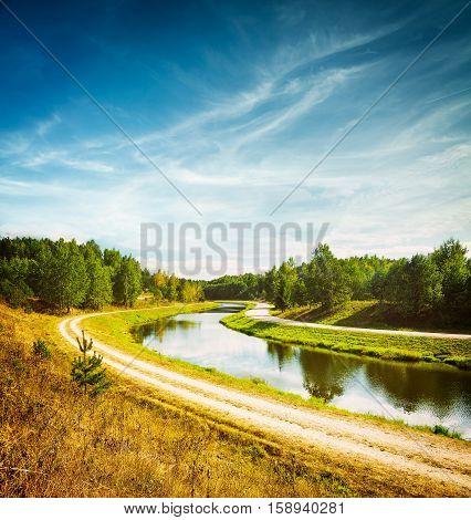 Summer Landscape with River and White Clouds at Blue Sky. Beautiful Non Urban Scenery. Road near the River. Scenic Nature Background. Toned and Filtered Photo with Copy Space.