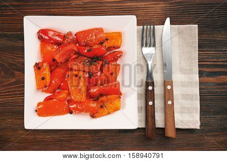 Grilled bell pepper on plate on wooden background, top view
