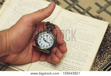 Old pocket watch in the hand on the background of the book