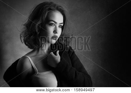 sensual sad young woman undressing on black background, monochrome