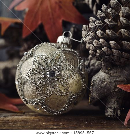 closeup of an ornamented christmas ball, some dry leaves, some branches, and some pine cones on a wooden rustic surface