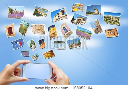 Female hands are holding a smart phone with a blank screen. On the blue sky are flying photos with sights of Provence. All buttons and potential trademarks on the phone are removed.