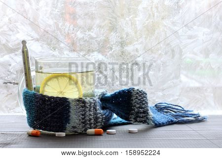 drink with lemon in the transparent mug wrapped in a scarf with a thermometer on the background of pills and frozen windows / prevention of colds in winter