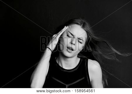 Young girl holding head as headaches. BW