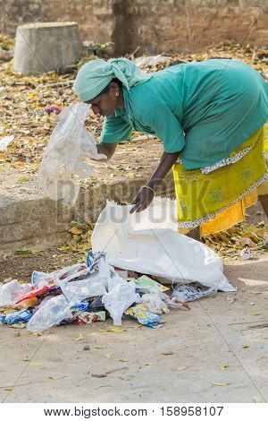 Pondicherry, Tamil Nadu, India - March 03, 2014. Household waste pastic pick up in the village. Women workers Plastic bottles, papers, bin