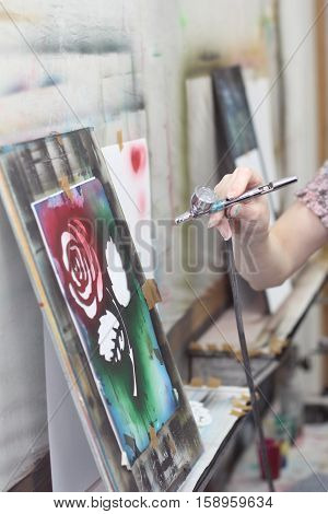 a Airbrush in hand paints brightly colored pictures with flower in a artistical studio