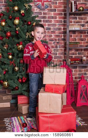 Smiling boyl standing on the floor next to the presents and a tree