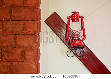 Interior detail red latern on white wall decorated with wood and stone