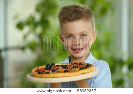 Cute boy with hot pizza at home