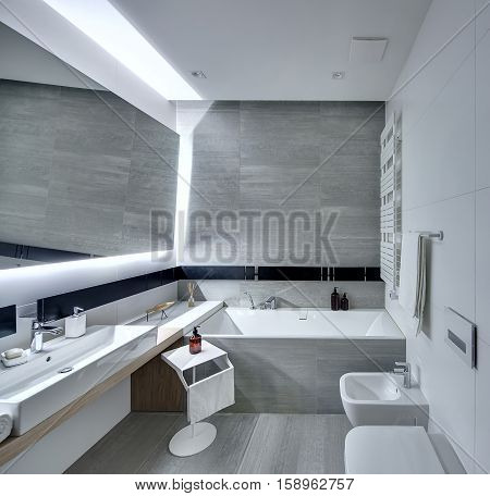Modern bathroom tiled with the white and gray tiles. There is a white sink with a soap, large mirror, bath, towel holder, towel radiator, toilet and a bide, stand with a towel and a pump bottle.