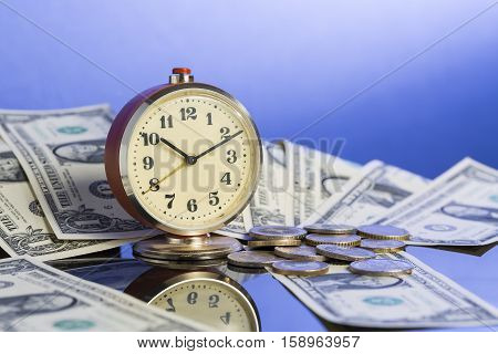 Business concept. Time is money. Vintage clock near american dollar cash and coins with nice blue gradient background.