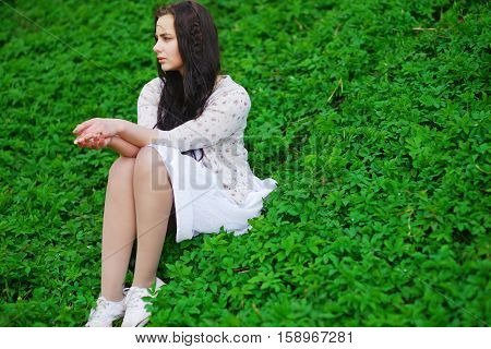 Cute long-haired girl sitting on the green lawn and looks to the side