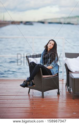 Beautiful brunette in a blue denim jacket and a black scarf sitting in a chair on the pier with downcast eyes on the background the blurred outlines of bridge and building in St. Petersburg.