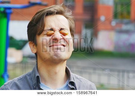 Young funny guy having fun by putting two acorns in the eyes on the Playground in the yard