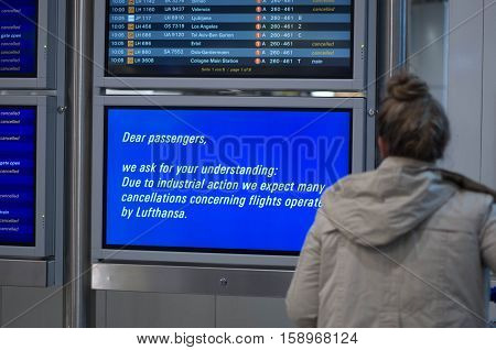 Frankfurt am Main, Hessen, Germany - November 29, 2016: Passenger looking at flight information board displaying cancelled Lufthansa flights due to strike by pilots in Frankfurt am Main airport