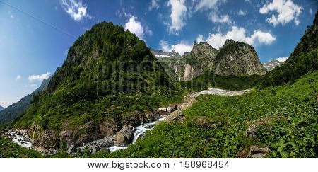 Nature view, cool mountain river stream flowing from under the glacier on background of mountain sierra. Highland pass in Upper Kodori District near border of Georgia - Abkhazia