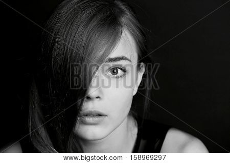 Young beautiful girl the hair on the eyes. BW