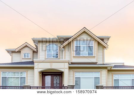 A perfect neighborhood. Houses in suburb at Fall in the north America. Top of a luxury house with nice window over dramatic pink clouds in the sky.