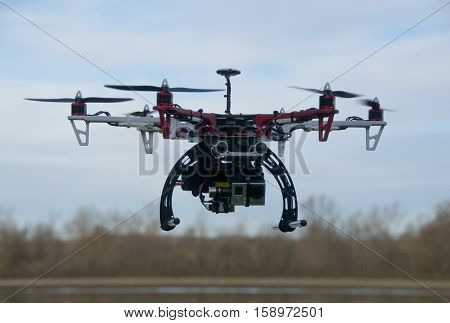 FELMERSHAM, UK - January 10, 2014: An Opto 30A Hex-a-copter with a Hero HD camera in flight  being controlled by it's owner by the Great River Ouse at Felmersham in Bedfordshire, England.