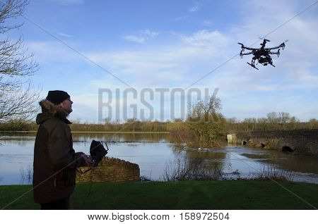 FELMERSHAM, UK - 10 January 10, 2014: An Opto 30A Hex-a-copter with a Hero HD camera in flight  being controlled by it's owner by the Great River Ouse at Felmersham in Bedfordshire, England.