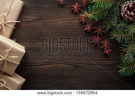 Christmas composition on wooden background with Christmas tree, pine cones, star anise and cardboard boxes. Christmas gift, pine cones, fir branches. Flat lay, top view