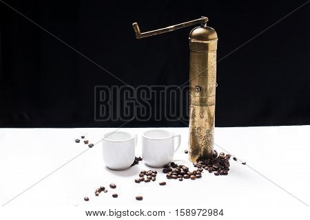 Two coffee cups, coffee seeds and coffee mill