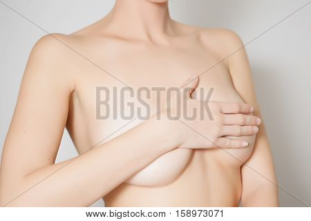 Woman examines her breast, close up photo