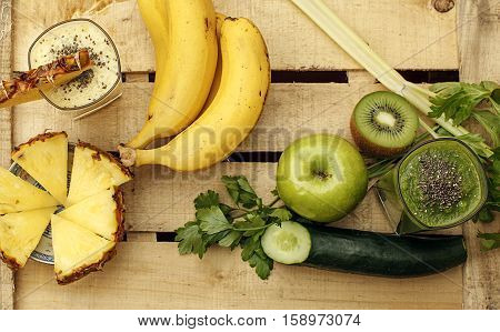 Healthy yellow and green smoothies or shakes made of banana pineapple apple cucumber celery parsley and chia with fruits and vegetables on the wooden background. Selective focus.