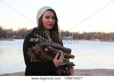 A young lady caring fire wood for a fire