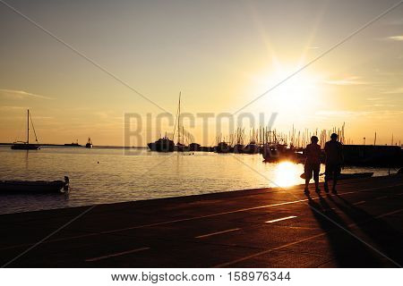Beautiful quay near the sea on sunset. People are walking near the water. Ships yachts and catters moored to the pier. Silhouetees of seniors couple