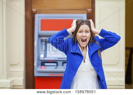 Frustrated young woman stands on against ATM in a shopping center