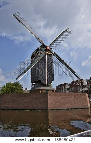 Black windmill along side the canals of Leiden, NL